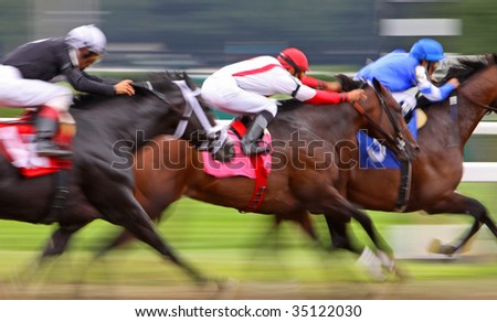 Slow shutter speed rendering of three jockeys racing their horses for the win in a thoroughbred horse race.