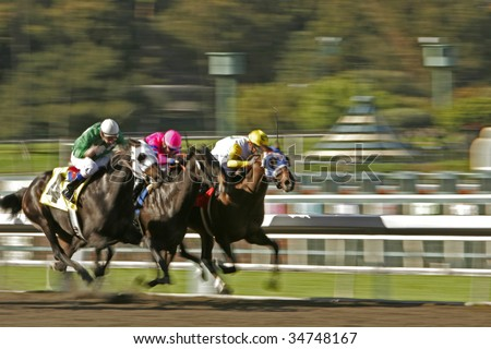 Slow shutter speed rendering of three racing jockeys and horses