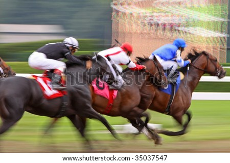 Slow shutter speed rendering of three racing jockeys and thoroughbreds