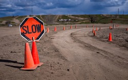 Slow Sign on Dirt Road with Cones