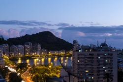 Slowshutter photo of Rio de Janeiro's lake lit up by city lights in the late afternoon.
