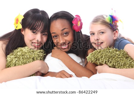 Slumber party for three teenage girl friends, a mixed race african american, oriental Japanese and blonde caucasian school mates all wearing flower or feather hair accessories.