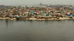 Slums in Manila near port on the bank of a river polluted with garbage, aerial view.