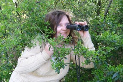sly curious European adult woman holding black field binoculars with zoom in her hands, hiding in greenery, peeping out of green bushes, spying on unfaithful husband, neighbors, nature observation