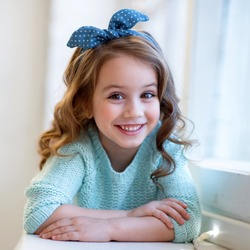 sly girl with accessories in her hair blue blouse and jeans smiling. fashion