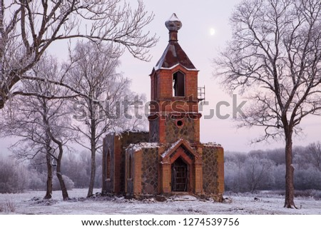 Small abandoned Orthodox church built of granite boulders and red bricks on cold winter evening, between big trees, with moon in sky.