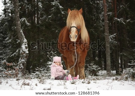 Small adorable girl sitting in the snow in forest and big palomino horse standing near