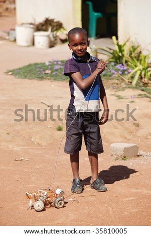 small African boy , outdoors, playing with a car made out of beer cans
