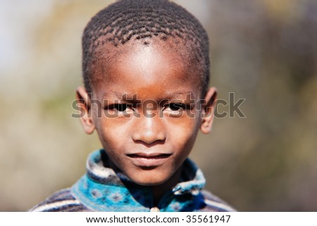 small african boy portrait , outdoors,blurred vegetation background