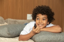 Small afro boy lying in bed with a remote control changing the tv channel
