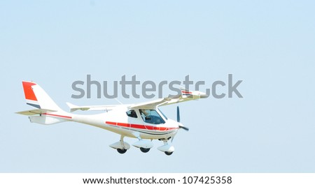 Small airplane flying against blue sky at airshow