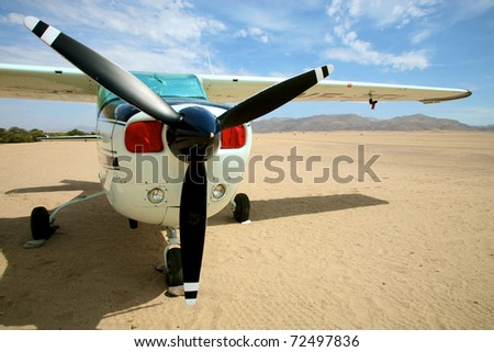 Small airplane in the desert of namibia with a blue sky and the sert all around