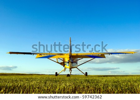 small airplane waiting on field