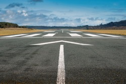 Small airport asphalt runway with markings for landings. Blue cloudy sky and fields around. Nobody.