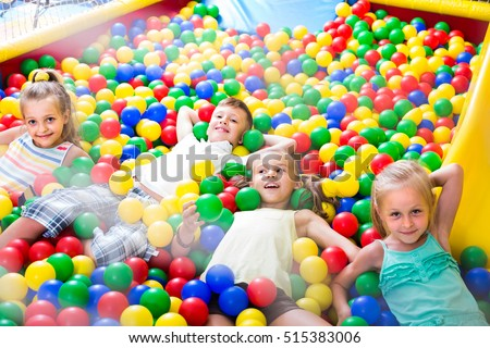 small american children playing together in pool with plastic multicolored balls #515383006