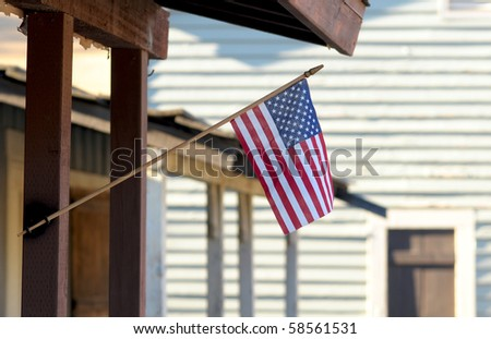 Small American Flag displayed on the front of an old rustic building