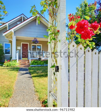 Small American house and white fence with red roses.