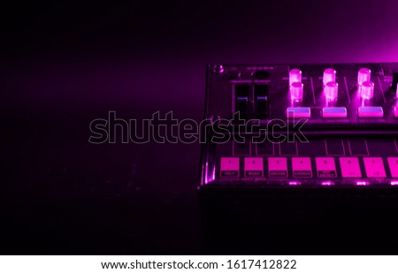 Small analog fm modulation synthesizer close up, selected focus, with knobs and faders, with effects arpeggiator and sequencer, colored lighting, black background, copy paste, music producer concept t