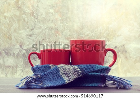 small and big red mug wrapped in a blue scarf and standing on the table against the background of a winter window / warming atmosphere for hanging out