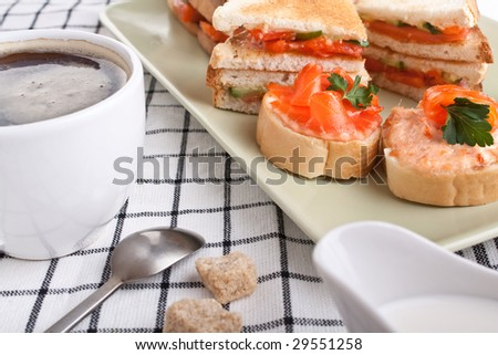 small and club salmon   sandwiches and a cup of coffee