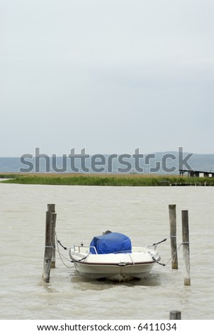 Small and covered motorboat moored between four piers near the seaside of Lake Neusiedl, Neusiedlersee, Burgenland, Austria
