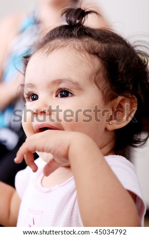 Small and cute girl with her hand in his mouth and smiling