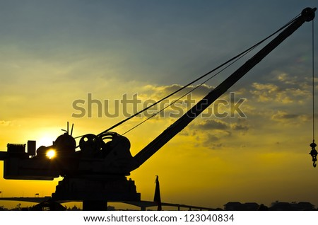 small and old crane in sunset