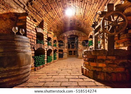 Small and old wine cellar with many full bottles and keg