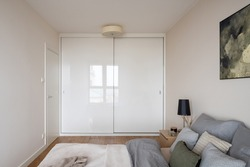 Small and simple bedroom with comfortable bed and big white wardrobe with sliding doors