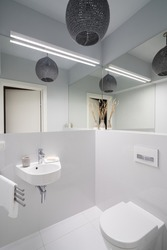 Small and stylish lavatory with white tiles, toilet and washbasin, led lights and mirror walls