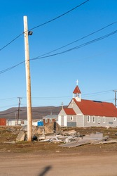 Small anglican church in the Canadian arctic in the golden hour.  St. Michael and All Angels Church in remote Inuit community of Qikiqtarjuaq, Broughton Island, Nunavut.