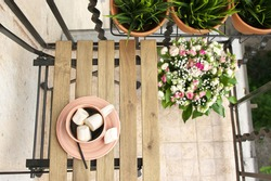 Small apartment balcony decor with folding wood chair and garden.
