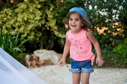Small Arabic girl with curly hair, wearing pink t-shirt and jeans shorts and jeans cap, smiling, laughing