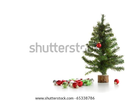 Small artificial tree with ornaments on white background
