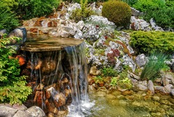 Small artificial waterfall in man made  tropical garden