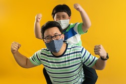 Small Asian son sits on strong dad shoulders showing biceps on yellow yellow background. Asian family enjoys activity games at home, a healthy fit lifestyle, two superheroes, happy Father Day concept.