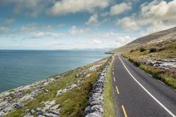Small asphalt road by Atlantic ocean, Burren National geo park, Ireland. Nobody, Warm sunny day. Beautiful cloudy blue sky. Part of Wild Atlantic Way.