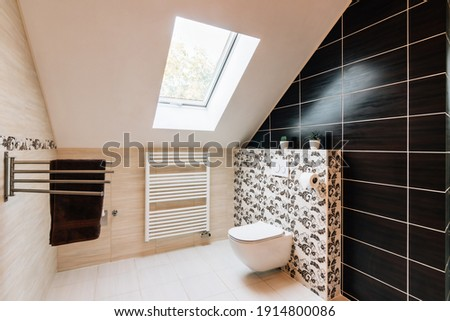 Small attic bathroom with sunroof. The tiling is in brown and beige colors variegated with texture of leaves. There is modern toilet, heating ladder and towel holder with brown towel in the bathroom. Foto stock ©