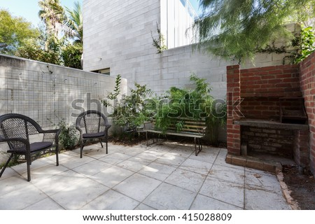 Small Australian apartment courtyard with paving and cane outdoor chairs