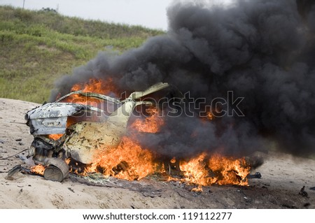 Small automobile that is burning and pouring out smoke