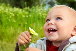 small baby boy holding a daisy in his hand and laughing in the field of flowers