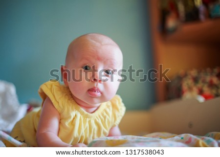 small baby confidently holds her head. first skills of child. Baby with confident pensive sight. Serious emotion or expresssi #1317538043