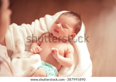 Small baby girl sleeping on mothers hands closeup. Top view. Woman holding infant girl. Motherhood.