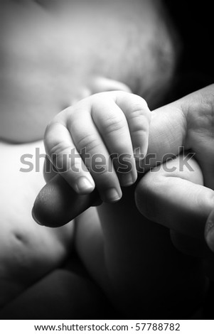 Small Baby hand holding Mother's finger