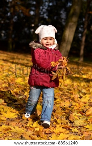 Small baby in autumn forest with yellow maple leaves