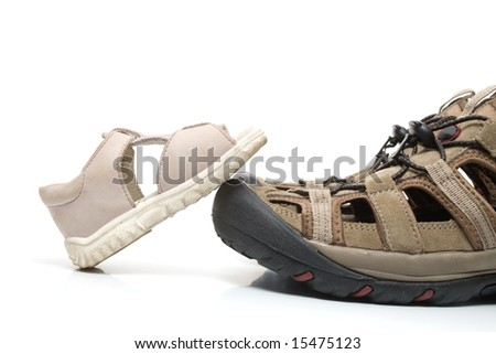 Small baby sandal stepping on huge adult shoe, isolated, on white background
