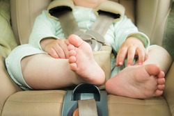 Small baby sitting in special car seat with safety seabelts, Safety in car concept, protection of child in travel, children feet in baby seat
