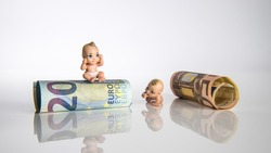 Small baby toys and euro money with white background, children figures with euro bank notes
