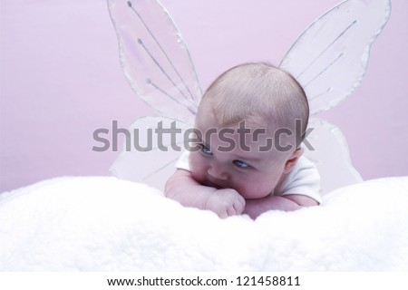 Small baby wearing angelic wings similar to butterfly/fairy against pink delicate background - stock photo