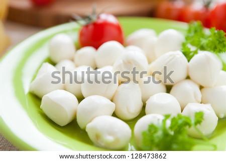 small balls of mozzarella on green plate, closeup